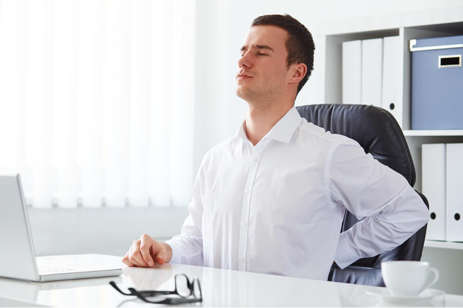 Working at a desk for prolonged periods can cause lower back pain (Photo: Adobe Stock)