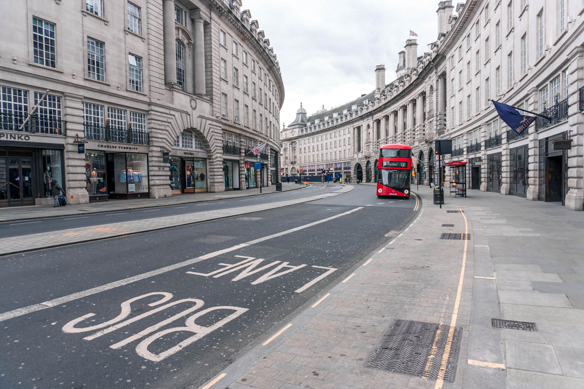 A bus pulls up at an empty bus stop on Oxford Street in London